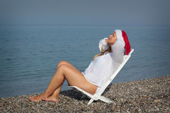 Christmas vacation. Woman in santa hat sitting on the beach Stock Photo