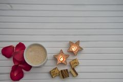 Romantic winter photography image with hot frothy milk drink and luxury chocolates and red rose petals and star shape lit candles Royalty Free Stock Photo