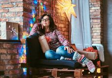 Happy beautiful girl enjoying Christmas morning while sitting on a couch with gift boxes in a decorated room with loft stock images