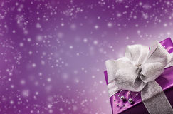 Christmas or Valentine's purple gift with silver ribbon abstract purple background. Christmas time Stock Images