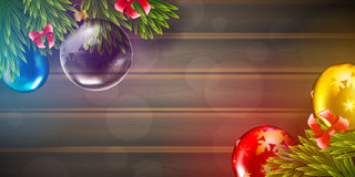 Christmas vector background with fir tree branch and color bulbs on wooden background Royalty Free Stock Images