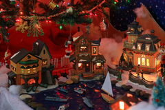 Christmas Village Houses under a tree. Christmas figurines from a holiday village display under a Christmas Tree Royalty Free Stock Image