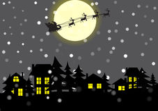 Christmas village and Santa Claus in the background of the moon. Silhouette of the city with illuminated windows. Above the town of Santa Claus is flying on the Stock Image