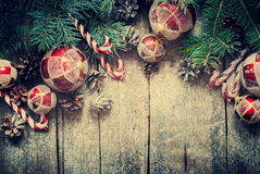 Christmas Vintage Fir Tree Toys, Red Balls, Coniferous, Candy Cane, Pine Cones on Wooden Planks. Toned Royalty Free Stock Image