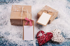 Christmas vintage gift boxes and heart shape decorations  on snow. Christmas presents with copy space blank tags. New year, love, Royalty Free Stock Image
