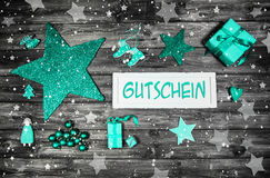 Christmas voucher or coupon with text in german language with mi. Nt green decoration on wooden background with sign Royalty Free Stock Images