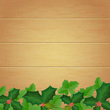 Christmas wallpaper with ivy, holly and fir branches on the back. Ground of wooden boards  For use as logos on cards, in printing, posters, invitations, web Royalty Free Stock Photo