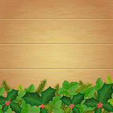 Christmas wallpaper with ivy, holly and fir branches on the back. Ground of wooden boards  For use as logos on cards, in printing, posters, invitations, web Royalty Free Stock Images