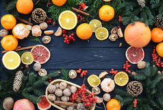 Christmas Wallpaper. With tangerines, oranges, nuts, grapefruit, kiwi, persimmons, cinnamon, cranberry, gingerbread and Christmas tree branches with cones on a Royalty Free Stock Photos