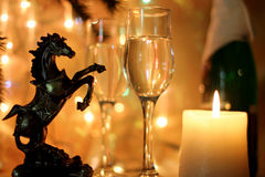 Christmas Wallpaper year of the horse. New Years Eve celebration background with an elegant arrangement with flutes and bottle of champagne and burning candles Royalty Free Stock Image