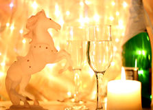 Christmas Wallpaper year of the horse. New Years Eve celebration background with an elegant arrangement with flutes and bottle of champagne and burning candles Stock Images