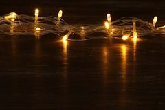 Christmas warm gold garland lights on balck wooden background. Royalty Free Stock Photo