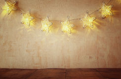 Christmas warm gold garland lights on wooden rustic background Stock Image