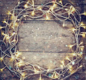 Christmas warm gold garland lights on wooden rustic background. filtered image Stock Photos