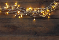 Christmas warm gold garland lights on wooden rustic background. filtered image Royalty Free Stock Photography