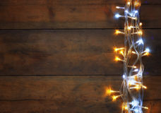 Christmas warm gold garland lights on wooden rustic background. filtered image. Royalty Free Stock Photography
