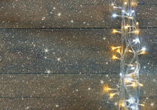 Christmas warm gold garland lights on wooden rustic background. filtered image with glitter overlay. Stock Images