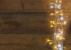 Christmas warm gold garland lights on wooden rustic background. filtered image with glitter overlay. Stock Image
