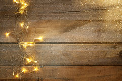 Christmas warm gold garland lights on wooden rustic background. Image of Christmas warm gold garland lights on wooden rustic background. glitter overlay Stock Photography