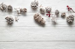 Christmas white background. Rustic garland with fir cones, red berries and snowy stars. Copy space below stock images