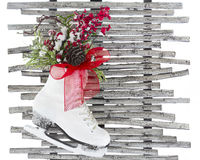 Christmas White Ice Skate Shoes Red Ribbon Pine Cone Wood Rustic. Christmas white ice skating shoes with red ribbon and Christmas bouquet hanging on the wood Royalty Free Stock Photo
