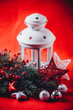 Christmas white lantern is standing with a burning candle in it with a fir tree branch and knit stars on a red background. Stock Photo