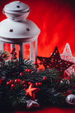 Christmas white lantern is standing with a burning candle in it with a fir tree branch and knit stars on a red background. Royalty Free Stock Image