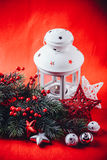 Christmas white lantern is standing with a burning candle in it with a fir tree branch and knit stars on a red background. Stock Photos