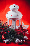 Christmas white lantern is standing with a burning candle in it with a fir tree branch and knit stars on a red background. Royalty Free Stock Images