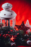Christmas white lantern is standing with a burning candle in it with a fir tree branch and knit stars on a red background. Royalty Free Stock Photography