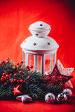 Christmas white lantern is standing with a burning candle in it with a fir tree branch and knit stars on a red background. Royalty Free Stock Photos