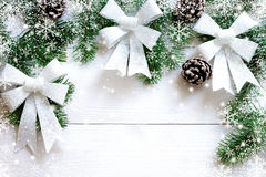 Christmas white wooden background with fir branches and bow Royalty Free Stock Image