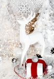 Christmas, white xmas white reindeer, gift with red ribbon, mountain ash, rowan, christmas tree and balls, on white background, royalty free stock photo