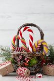 Christmas basket with candy canes on white planks Stock Photo