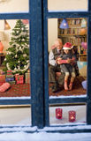 Christmas window. Grandfather giving Christmas present to his little granddaughter watched from a snowy window Royalty Free Stock Photo