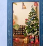 Christmas window. Little girl hiding behind a Christmas tree watched from a window Stock Photography