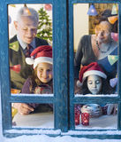 Christmas window. Grandparents and granddaughter at the window on Christmas eve Royalty Free Stock Photo