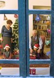 Christmas window. Grandparents giving Christmas present to thier little granddaughters Stock Image