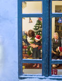 Christmas window. Grandparents giving Christmas present to their little granddaughters Royalty Free Stock Images