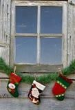 Christmas stockings on garland under window Royalty Free Stock Photos