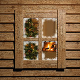 Christmas window. Christmas tree and fireplace seen through an old window Royalty Free Stock Images
