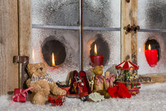 Christmas window decoration: candles with old children toys. Royalty Free Stock Photo