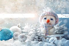 Christmas winter background with a small snowman and Christmas ornaments.Happy New Year and Merry Christmas. Background with copy space Royalty Free Stock Image