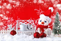 Christmas winter background with a small snowman and Christmas ornaments. Merry Christmas and Happy New Year. Royalty Free Stock Image