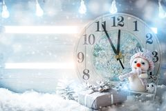 Christmas winter a background, the small snowman stands with a clock. Happy New Year. Merry Christmas. Royalty Free Stock Photo
