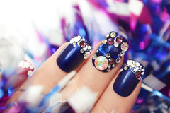 Christmas winter blue manicure . Christmas winter blue manicure with rhinestones of different shapes and sparkles of snow on female hand with a garland royalty free stock images