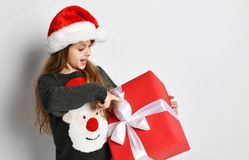 Smiling Christmas little girl kid in x-mas santa helper hat with red gift box happy smiling. Christmas winter concept - smiling little girl kid in x-mas santa stock photo