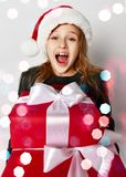 Little girl kid in x-mas santa helper hat with red gift boxes happy smiling shouting. Christmas winter concept - smiling little girl kid in x-mas santa helper royalty free stock photo