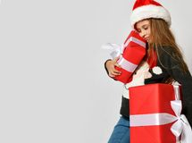 Little girl kid in x-mas santa helper hat with red gift boxes happy smiling shouting. Christmas winter concept - smiling little girl kid in x-mas santa helper stock images