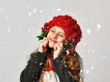 Christmas winter concept - smiling little girl kid in x-mas santa helper red hat happy smiling. On white background under snow stock photography